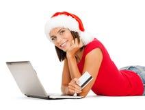 Femme dans le chapeau de Santa avec l'ordinateur portable et la carte de crédit Photo libre de droits