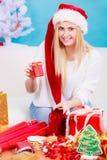 Femme dans le chapeau de Santa préparant des cadeaux de Noël photographie stock libre de droits