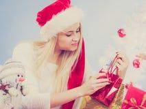Femme dans le chapeau de Santa préparant des cadeaux de Noël Photographie stock