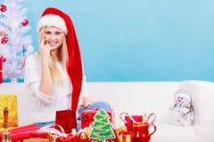 Femme dans le chapeau de Santa préparant des cadeaux de Noël Images libres de droits