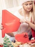 Femme dans le chapeau de Santa préparant des cadeaux de Noël Images stock