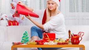 Femme dans le chapeau de Santa préparant des cadeaux de Noël photo libre de droits