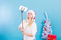 Femme dans le chapeau de Santa prenant le selfie photographie stock libre de droits