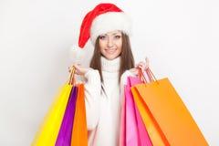Femme dans le chapeau de Santa retenant des sacs ? provisions Photographie stock libre de droits