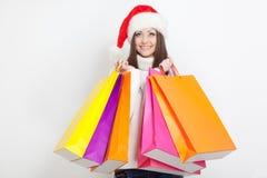 Femme dans le chapeau de Santa retenant des sacs ? provisions Photographie stock