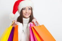 Femme dans le chapeau de Santa retenant des sacs ? provisions Image stock