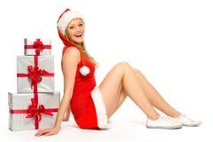 Femme dans le chapeau de Santa se reposant près des cadeaux de Noël image libre de droits
