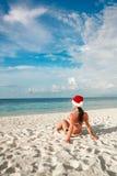Femme dans le chapeau de Santa sur la plage Photos libres de droits