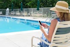 Femme dans le chapeau de soleil détendant par la piscine en été images stock