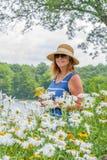 Femme dans le chapeau de soleil et lunettes de soleil sélectionnant des wildflowers au lac photos libres de droits