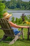 Femme dans le chapeau de soleil se reposant dans la chaise d'Adirondack le long du lac images stock