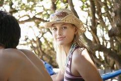 Femme dans le chapeau de soleil se reposant près de l'ami dehors Image libre de droits