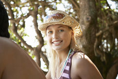 Femme dans le chapeau de soleil se reposant près de l'ami dehors Images stock