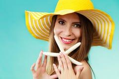 Femme dans le chapeau jaune tenant la coquille blanche photo stock
