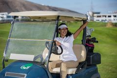 Femme dans le chariot de golf sur des amis de salutation de champ Photographie stock