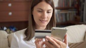 Femme dans le chemisier blanc se reposant sur le sofa dans le salon achetant en ligne avec la carte de crédit sur le smartphone banque de vidéos