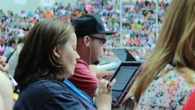 Femme dans le chemisier foncé sur des types de supports de spectateurs sur la Tablette banque de vidéos