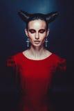 Femme dans le costume de carnaval. forme de sorcière avec des klaxons. Image stock