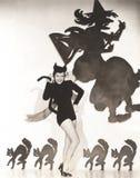 Femme dans le costume de chat posant contre le mur orienté de Halloween photo stock
