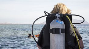 Femme dans le costume de plongée avec le scaphandre autonome prêt à plonger dans la mer photos stock