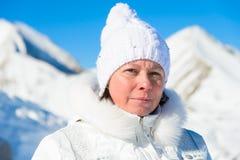Femme dans le costume de ski sur un fond des montagnes Photographie stock