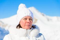 Femme dans le costume de ski sur un fond des montagnes Images stock