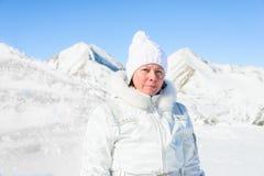 Femme dans le costume de ski sur un fond des montagnes Photos stock