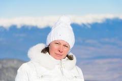Femme dans le costume de ski sur un fond des montagnes Photo stock