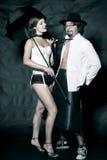 Femme dans le costume et l'homme sexy dans la chemise blanche avec le lien noir et le chapeau Images stock