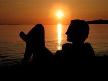 Femme dans le coucher du soleil sur la plage Photographie stock libre de droits