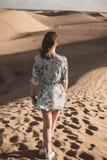 Femme dans le désert avec la robe florale intéressante regardant l'horizon image libre de droits