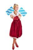 Femme dans le dirndl avec les drapeaux bavarois Photo stock