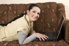 Femme dans le divan avec l'ordinateur portatif Photos stock