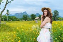 Femme dans le domaine de fleur jaune de cosmos images libres de droits
