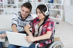 Femme dans le fauteuil roulant avec l'aide d'ami Image libre de droits