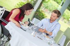 Femme dans le fauteuil roulant avec le mari dans le restaurant Image stock