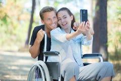Femme dans le fauteuil roulant et l'ami prenant le selfie avec le smartphone Photographie stock libre de droits