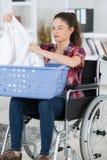 Femme dans le fauteuil roulant faisant la blanchisserie image libre de droits