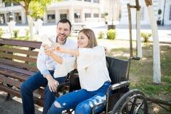 Femme dans le fauteuil roulant prenant le selfie avec un type Images stock