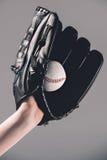 Femme dans le gant de base-ball tenant la boule sur le gris Photographie stock libre de droits
