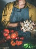 Femme dans le groupe de participation de tablier d'ail pour la cuisson images stock