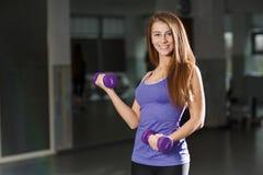 Femme dans le gymnase s'exerçant avec des haltères Photographie stock libre de droits