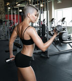 Femme dans le gymnase s'exerçant avec des haltères Image stock