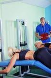 Femme dans le gymnase s'exerçant avec le trai personnel de forme physique images stock