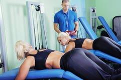 Femme dans le gymnase s'exerçant avec le trai personnel de forme physique photos stock