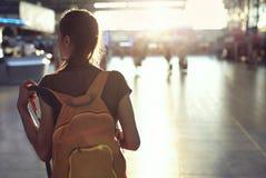Femme dans le hall du terminal d'aéroport avec le petit sac à dos Photographie stock