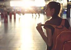 Femme dans le hall du terminal d'aéroport avec le petit sac à dos Images stock