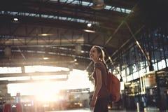 Femme dans le hall du terminal d'aéroport avec le petit sac à dos Photo stock