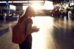 Femme dans le hall du terminal d'aéroport avec un passeport et une carte d'embarquement Photo libre de droits