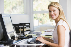 Femme dans le Home Office avec le sourire d'ordinateur